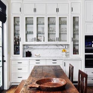 Aménagement d'une cuisine américaine classique avec un placard avec porte à panneau encastré, des portes de placard blanches, une crédence blanche, un électroménager en acier inoxydable, un sol en bois foncé, un plan de travail en marbre, une crédence en marbre, un îlot central et un sol marron.