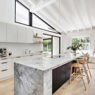 Photo of a mid-sized transitional l-shaped open plan kitchen in Sydney with an undermount sink, flat-panel cabinets, dark wood cabinets, granite benchtops, white splashback, matchstick tile splashback, black appliances, light hardwood floors, with island, beige floor, grey benchtop, exposed beam and vaulted.