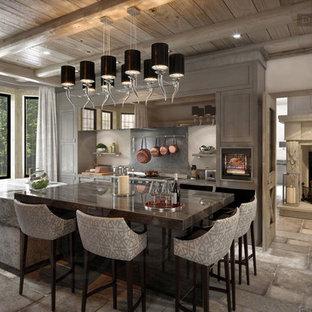 На фото: класса люкс большие кухни в стиле кантри с искусственно-состаренными фасадами, столешницей из оникса, серым фартуком, полом из известняка и двумя и более островами