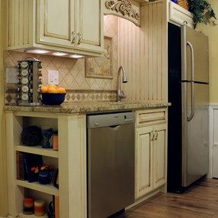 Kleine Klassische Wohnküche mit Unterbauwaschbecken, profilierten Schrankfronten, Granit-Arbeitsplatte, Rückwand aus Steinfliesen, Küchengeräten aus Edelstahl, Laminat und Halbinsel in Philadelphia