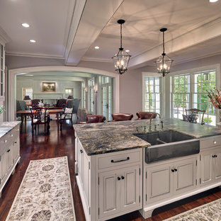 Design ideas for a mid-sized traditional u-shaped eat-in kitchen in Other with raised-panel cabinets, white cabinets, limestone benchtops, with island, multi-coloured benchtop, a farmhouse sink, white splashback, marble splashback, panelled appliances, dark hardwood floors and brown floor.