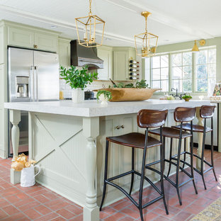 Photo of a mid-sized mediterranean l-shaped eat-in kitchen in Baltimore with a farmhouse sink, quartz benchtops, stainless steel appliances, brick floors, with island, shaker cabinets, green cabinets, white splashback, subway tile splashback and red floor.