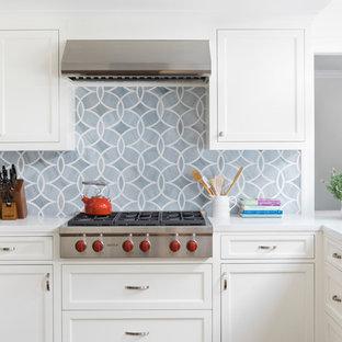 Создайте стильный интерьер: п-образная кухня в стиле современная классика с накладной раковиной, белыми фасадами, столешницей из кварцевого композита, серым фартуком, фартуком из стеклянной плитки, островом, фасадами с утопленной филенкой, техникой из нержавеющей стали и пробковым полом - последний тренд