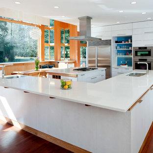 Immagine di una cucina a L contemporanea con lavello a doppia vasca, top in quarzo composito, ante lisce, ante bianche, elettrodomestici in acciaio inossidabile, paraspruzzi blu e paraspruzzi con lastra di vetro
