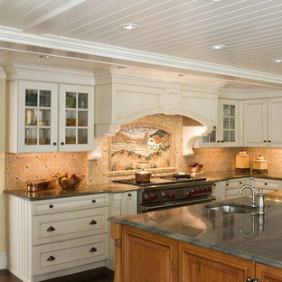 Traditional kitchen designs - Elegant kitchen photo in Boston with glass-front cabinets, beige cabinets, granite countertops and multicolored backsplash