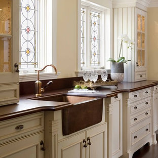 Example of a classic kitchen design in Boston with recessed-panel cabinets, a farmhouse sink, wood countertops, beige cabinets and brown countertops