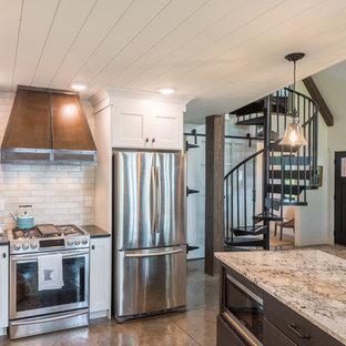 ミネアポリスの中サイズのラスティックスタイルのおしゃれなキッチン (ドロップインシンク、シェーカースタイル扉のキャビネット、白いキャビネット、人工大理石カウンター、ベージュキッチンパネル、サブウェイタイルのキッチンパネル、シルバーの調理設備の、コンクリートの床、グレーの床、黒いキッチンカウンター) の写真