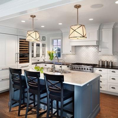 Elegant u-shaped dark wood floor kitchen photo in DC Metro with an undermount sink, shaker cabinets, white cabinets, white backsplash, subway tile backsplash, paneled appliances and an island