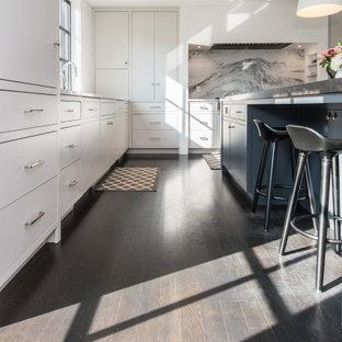 Esempio di una grande cucina design con lavello sottopiano, ante lisce, ante bianche, top in pietra calcarea, paraspruzzi grigio, paraspruzzi in marmo, elettrodomestici in acciaio inossidabile, parquet scuro, isola, pavimento nero e top nero
