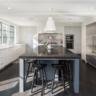 Foto på ett stort funkis svart kök, med en undermonterad diskho, släta luckor, vita skåp, bänkskiva i kalksten, grått stänkskydd, stänkskydd i marmor, rostfria vitvaror, mörkt trägolv, en köksö och svart golv