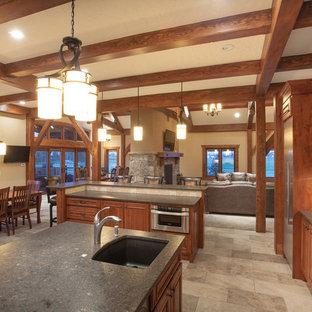 デンバーの広いラスティックスタイルのおしゃれなキッチン (アンダーカウンターシンク、落し込みパネル扉のキャビネット、中間色木目調キャビネット、ソープストーンカウンター、ベージュキッチンパネル、セラミックタイルのキッチンパネル、シルバーの調理設備、セラミックタイルの床) の写真