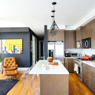 Trendy l-shaped medium tone wood floor open concept kitchen photo in San Francisco with flat-panel cabinets, dark wood cabinets, white backsplash, subway tile backsplash, stainless steel appliances, an island, an undermount sink and quartz countertops