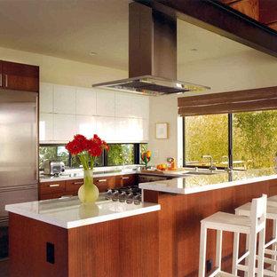 Immagine di una grande cucina moderna con ante lisce, ante in legno bruno, elettrodomestici in acciaio inossidabile, lavello sottopiano, top in superficie solida, pavimento in cemento, penisola e pavimento grigio