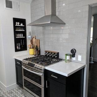 フェニックスの中くらいのシャビーシック調のおしゃれなキッチン (エプロンフロントシンク、フラットパネル扉のキャビネット、黒いキャビネット、珪岩カウンター、グレーのキッチンパネル、サブウェイタイルのキッチンパネル、シルバーの調理設備、セラミックタイルの床、アイランドなし、グレーの床、白いキッチンカウンター) の写真