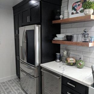フェニックスの中サイズのシャビーシック調のおしゃれなキッチン (エプロンフロントシンク、フラットパネル扉のキャビネット、黒いキャビネット、珪岩カウンター、グレーのキッチンパネル、サブウェイタイルのキッチンパネル、シルバーの調理設備の、セラミックタイルの床、アイランドなし、グレーの床、白いキッチンカウンター) の写真