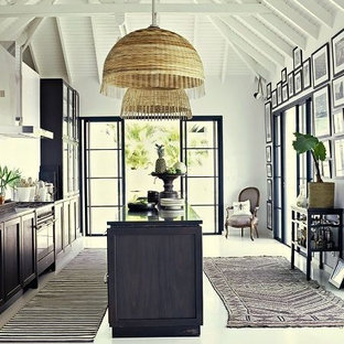 Inspiration for a mid-sized tropical galley open plan kitchen in Seattle with an integrated sink, flat-panel cabinets, blue cabinets, marble benchtops, white splashback, panelled appliances, medium hardwood floors and no island.