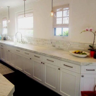 Mid-sized traditional eat-in kitchen pictures - Example of a mid-sized classic galley dark wood floor and brown floor eat-in kitchen design in Los Angeles with white cabinets, multicolored backsplash, stainless steel appliances, no island and multicolored countertops