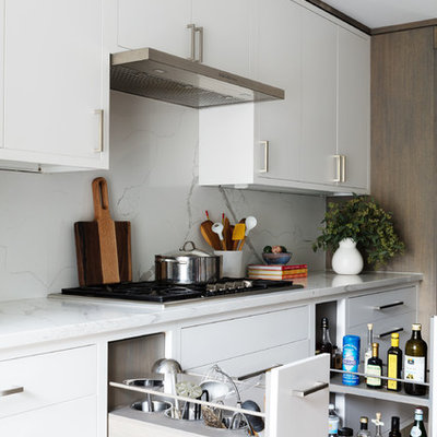 Inspiration for a mid-sized contemporary single-wall light wood floor and beige floor open concept kitchen remodel in New York with flat-panel cabinets, light wood cabinets, quartz countertops, white backsplash, marble backsplash, stainless steel appliances, an island and white countertops