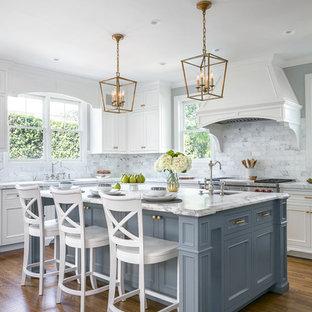 Foto di una cucina a L classica con lavello sottopiano, ante con riquadro incassato, ante grigie, paraspruzzi bianco, paraspruzzi in marmo, elettrodomestici in acciaio inossidabile, parquet scuro, isola e pavimento marrone