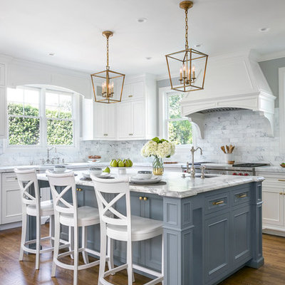Example of a classic l-shaped dark wood floor and brown floor kitchen design in San Francisco with an undermount sink, recessed-panel cabinets, gray cabinets, white backsplash, marble backsplash, stainless steel appliances and an island