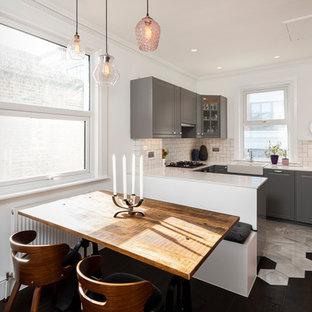 Foto på ett mellanstort vintage vit kök, med en rustik diskho, vitt stänkskydd, stänkskydd i tunnelbanekakel, svart golv, luckor med upphöjd panel, grå skåp och en halv köksö