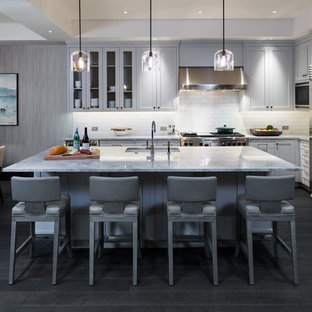Photo of a transitional l-shaped eat-in kitchen in Other with an undermount sink, shaker cabinets, grey cabinets, white splashback, subway tile splashback, stainless steel appliances, dark hardwood floors and with island.