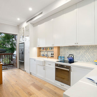 This is an example of a transitional l-shaped eat-in kitchen in Sydney with white cabinets, blue splashback, stainless steel appliances, a farmhouse sink, shaker cabinets, light hardwood floors, a peninsula, white benchtop and mosaic tile splashback.
