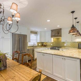 シカゴの中サイズのエクレクティックスタイルのおしゃれなキッチン (アンダーカウンターシンク、シェーカースタイル扉のキャビネット、白いキャビネット、御影石カウンター、緑のキッチンパネル、ガラスタイルのキッチンパネル、シルバーの調理設備、無垢フローリング、茶色い床) の写真