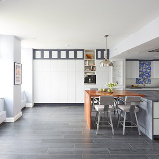Large contemporary eat-in kitchen remodeling - Example of a large trendy l-shaped cork floor eat-in kitchen design in Chicago with an undermount sink, flat-panel cabinets, white cabinets, wood countertops, gray backsplash, glass sheet backsplash, stainless steel appliances and two islands
