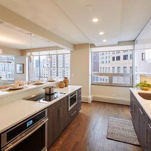 シカゴの大きいコンテンポラリースタイルのおしゃれなキッチン (アンダーカウンターシンク、ガラス扉のキャビネット、白いキャビネット、人工大理石カウンター、白いキッチンパネル、レンガのキッチンパネル、シルバーの調理設備の、濃色無垢フローリング、茶色い床、白いキッチンカウンター) の写真