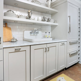 Small transitional enclosed kitchen designs - Example of a small transitional galley cork floor enclosed kitchen design in Chicago with a drop-in sink, beaded inset cabinets, gray cabinets, marble countertops, white backsplash, subway tile backsplash, paneled appliances and no island