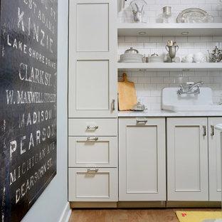 シカゴの小さいトランジショナルスタイルのおしゃれなキッチン (ドロップインシンク、フラットパネル扉のキャビネット、グレーのキャビネット、大理石カウンター、白いキッチンパネル、サブウェイタイルのキッチンパネル、パネルと同色の調理設備、コルクフローリング、アイランドなし) の写真