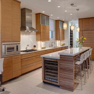 シカゴの中サイズのコンテンポラリースタイルのおしゃれなキッチン (フラットパネル扉のキャビネット、中間色木目調キャビネット、白いキッチンパネル、シルバーの調理設備の、アンダーカウンターシンク、セラミックタイルの床、ベージュの床、人工大理石カウンター) の写真