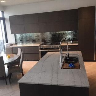 Foto di una grande cucina minimalista con lavello sottopiano, ante lisce, ante nere, top in quarzite, paraspruzzi a effetto metallico, paraspruzzi con piastrelle di metallo, elettrodomestici in acciaio inossidabile, pavimento in pietra calcarea e isola