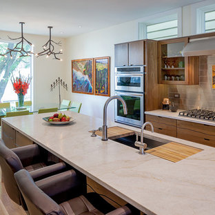 This is an example of a contemporary galley eat-in kitchen in Chicago with an undermount sink, flat-panel cabinets, medium wood cabinets, metallic splashback, metal splashback, stainless steel appliances, marble benchtops, medium hardwood floors and beige benchtop.