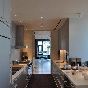 На фото: большая параллельная, отдельная кухня в современном стиле с техникой из нержавеющей стали, двойной раковиной, плоскими фасадами, серыми фасадами, столешницей из акрилового камня, ковровым покрытием и черным полом без острова