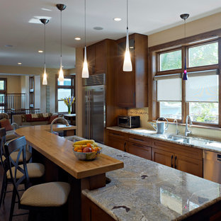 Large traditional open concept kitchen designs - Inspiration for a large timeless l-shaped dark wood floor open concept kitchen remodel in Chicago with medium tone wood cabinets, wood countertops, beige backsplash, stainless steel appliances, an undermount sink and recessed-panel cabinets