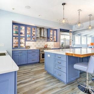 他の地域の大きいエクレクティックスタイルのおしゃれなアイランドキッチン (エプロンフロントシンク、レイズドパネル扉のキャビネット、青いキャビネット、大理石カウンター、マルチカラーのキッチンパネル、セメントタイルのキッチンパネル、シルバーの調理設備、磁器タイルの床、グレーの床、白いキッチンカウンター) の写真