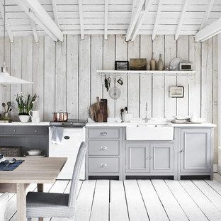 Diseño de cocina comedor lineal, de estilo de casa de campo, de tamaño medio, sin isla, con fregadero sobremueble, puertas de armario grises, suelo gris, suelo de madera pintada, armarios con rebordes decorativos, salpicadero de madera y electrodomésticos blancos