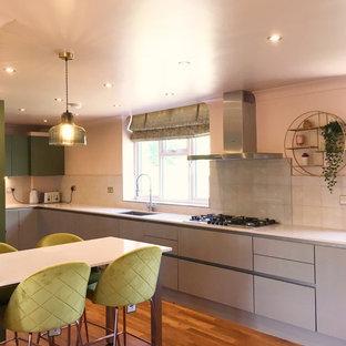 Idées déco pour une cuisine américaine en L de taille moyenne avec un plan de travail en quartz, une crédence rose, un sol en vinyl, une péninsule, un sol marron et un plan de travail rose.