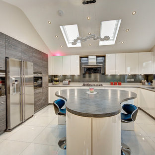 Photo of a large contemporary u-shaped kitchen in London with an island, flat-panel cabinets, white cabinets, grey splashback, stainless steel appliances and white floors.