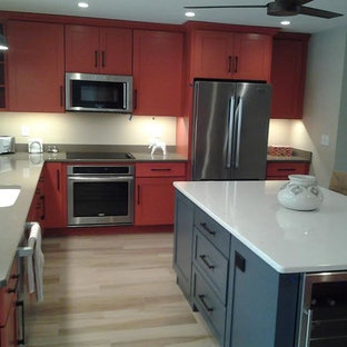 Photo of a mid-sized contemporary u-shaped eat-in kitchen in Tampa with an undermount sink, shaker cabinets, orange cabinets, solid surface benchtops, stainless steel appliances, vinyl floors and with island.