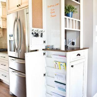 На фото: большая кухня в классическом стиле с фасадами с утопленной филенкой, белыми фасадами, деревянной столешницей и техникой из нержавеющей стали с