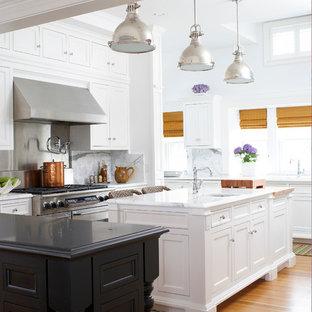 マイアミのヴィクトリアン調のおしゃれなキッチン (アンダーカウンターシンク、落し込みパネル扉のキャビネット、白いキャビネット、大理石カウンター、白いキッチンパネル、石スラブのキッチンパネル、シルバーの調理設備の、無垢フローリング) の写真