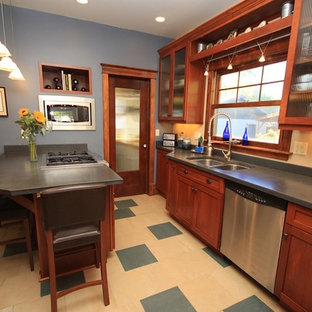 This is an example of a mid-sized arts and crafts galley open plan kitchen in Denver with a double-bowl sink, glass-front cabinets, dark wood cabinets, concrete benchtops, stainless steel appliances, porcelain floors and a peninsula.