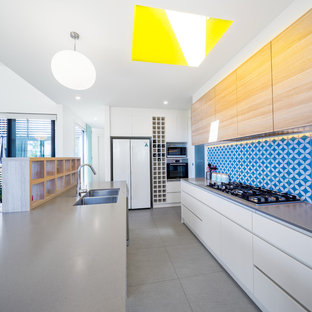 Mid-sized contemporary galley open plan kitchen in Canberra - Queanbeyan with white cabinets, quartz benchtops, blue splashback, cement tile splashback, with island, grey floor, a double-bowl sink, flat-panel cabinets, white appliances and grey benchtop.