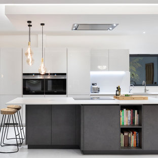This is an example of a medium sized contemporary galley open plan kitchen in London with flat-panel cabinets, grey cabinets, quartz worktops, grey splashback, stone slab splashback, black appliances, porcelain flooring, an island, grey floors, a submerged sink and white worktops.