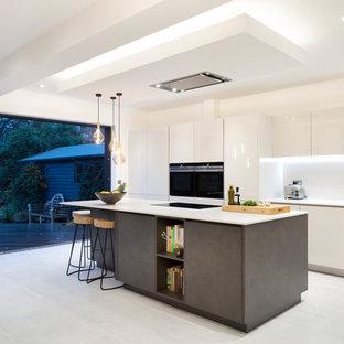 ロンドンの中サイズのエクレクティックスタイルのおしゃれなキッチン (一体型シンク、フラットパネル扉のキャビネット、グレーのキャビネット、珪岩カウンター、グレーのキッチンパネル、石スラブのキッチンパネル、黒い調理設備、磁器タイルの床、グレーの床、グレーのキッチンカウンター) の写真