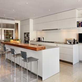 Design ideas for a contemporary kitchen in London with an integrated sink, flat-panel cabinets, grey cabinets, stainless steel worktops, beige splashback, stainless steel appliances, an island and beige floors.
