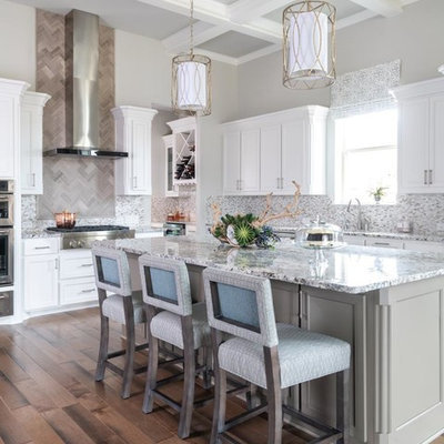Large transitional l-shaped medium tone wood floor and brown floor kitchen photo in Dallas with an undermount sink, recessed-panel cabinets, white cabinets, gray backsplash, mosaic tile backsplash, stainless steel appliances, an island and gray countertops